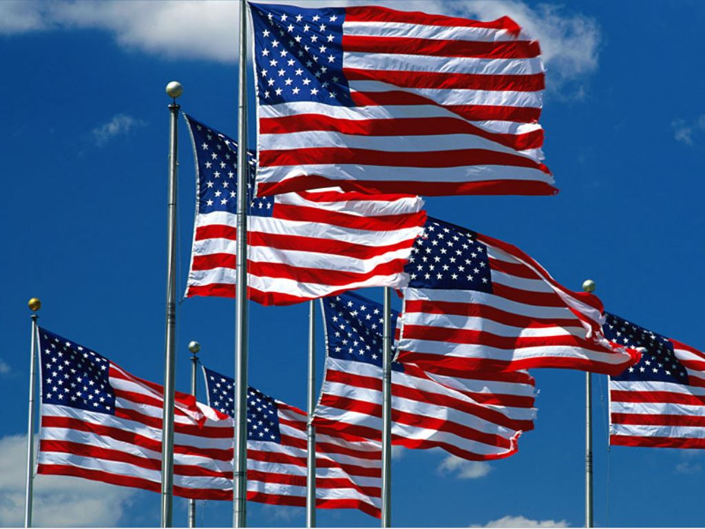 Several American flags against a blue sky