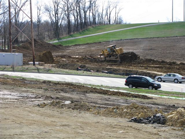 View of cars in parking lot and construction equipment moving dirt