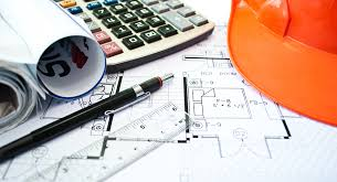 Image of desk with blueprints, calculator, pen and hardhat